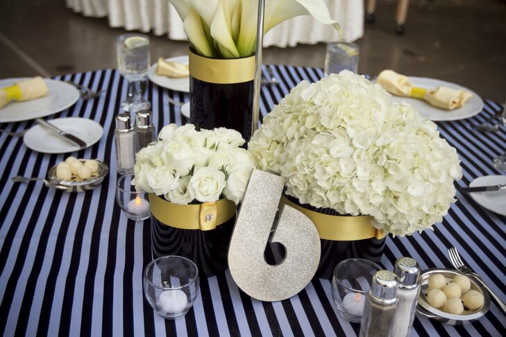 Black vases accented by yellow satin ribbon were filled with ivory roses, hydrangeas and calla lilies. Shimmery gold numbers in Art Deco style typeface added a hint of glam to the tablescape.