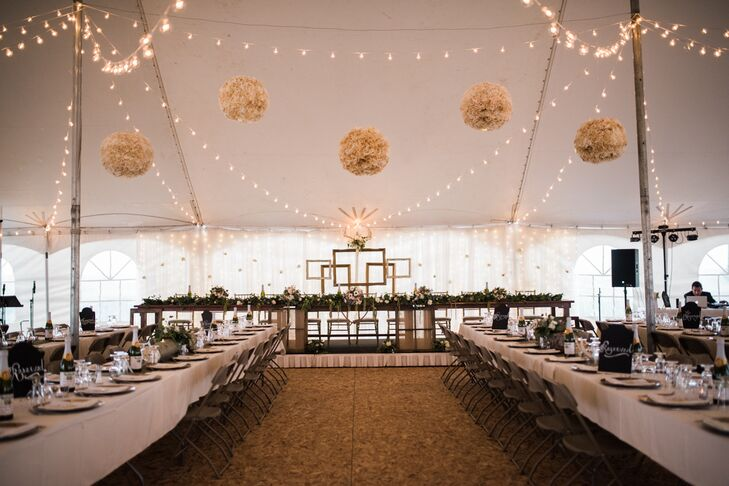 Julia and Matthew left no detail overlooked, from the wooden centerpieces to the handmade head table and antler accents. The tent ceiling was no different—strands of bistro lights glowed warmly as the sun began to set, and playful paper lanterns added a hint of visual drama to the room.