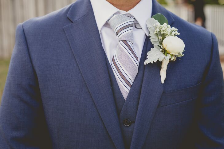 After selecting a dapper, three-piece navy suit, Rodney completed the look with few standout accessories. He wore a white shirt, a grand white peony and dusty miller boutonniere and a striped blue and white tie that brought it all together.