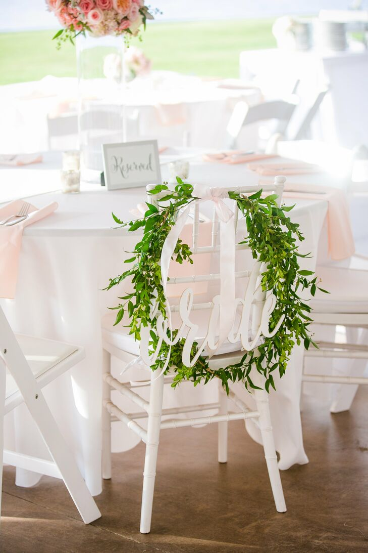 Wreaths of fresh greenery hung on the backs of chairs marking the bride's and groom's seats at the reception. Keeping with the theme, the wreaths were a simple, summery way to identify the bride's and groom's chairs.