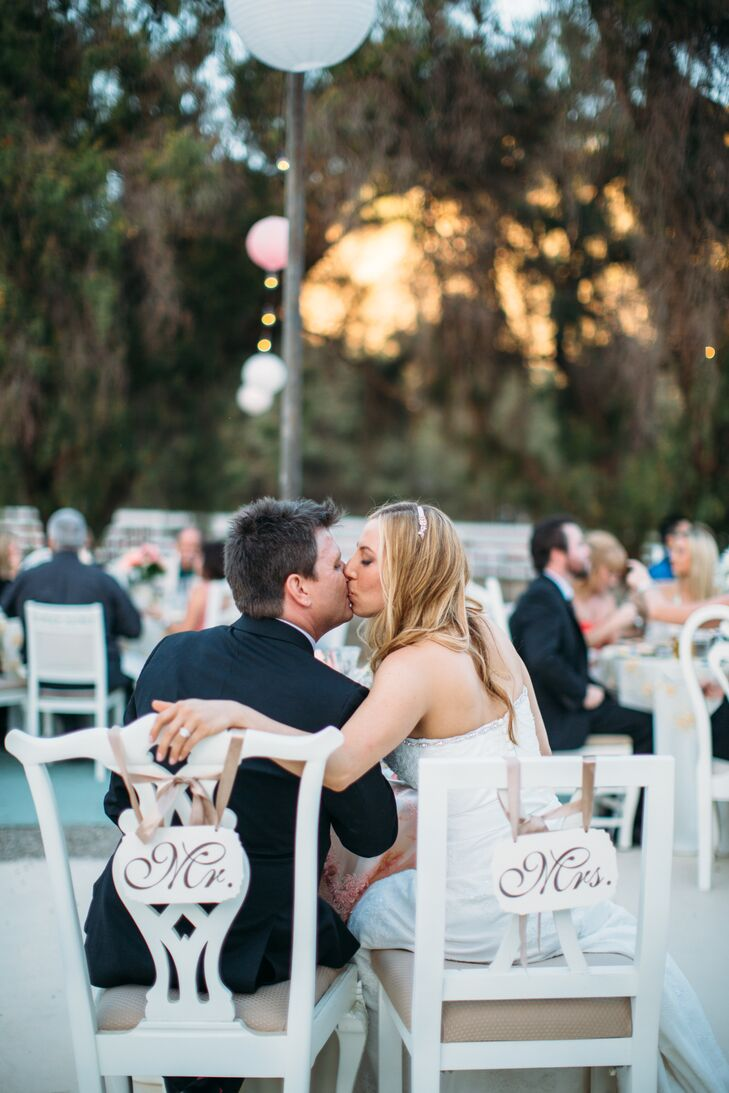 """Monique and Shade sat in white antique chairs at the sweetheart table, draped with white wooden """"Mr."""" and """"Mrs."""" signs hanging by champagne-colored ribbon."""