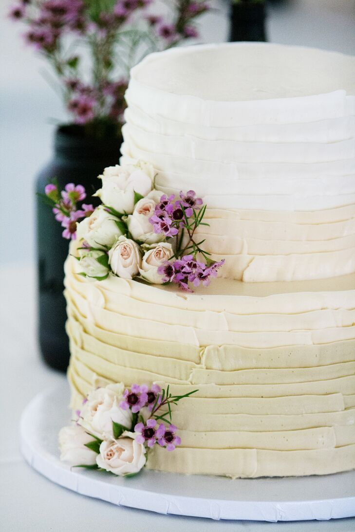 """The couple's two-tier six- and nine-inch round ombre cake used white frosting on top and champagne icing on the bottom. """"The top was raspberry swirl cake with a buttercream filling and the bottom was chocolate cake with a peanut butter filling,"""" Ashley says. """"Our florist had light purple spray roses and purple wax flowers set aside to decorate the cake."""""""