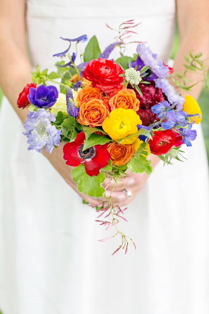 Since Maggie loves flowers, vibrant blooms in red, orange, yellow and purple filled the bridesmaid bouquets, groomsmen boutonnieres and ceremony arch. Maggie and Joe even matched the blooms to the custom floral-print bench cushions where guests sat during the outdoor ceremony.