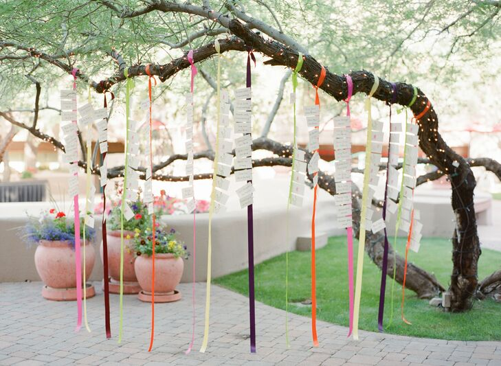 Escort cards hung from jewel-tone-hued ribbons that dangled from a tree branch.
