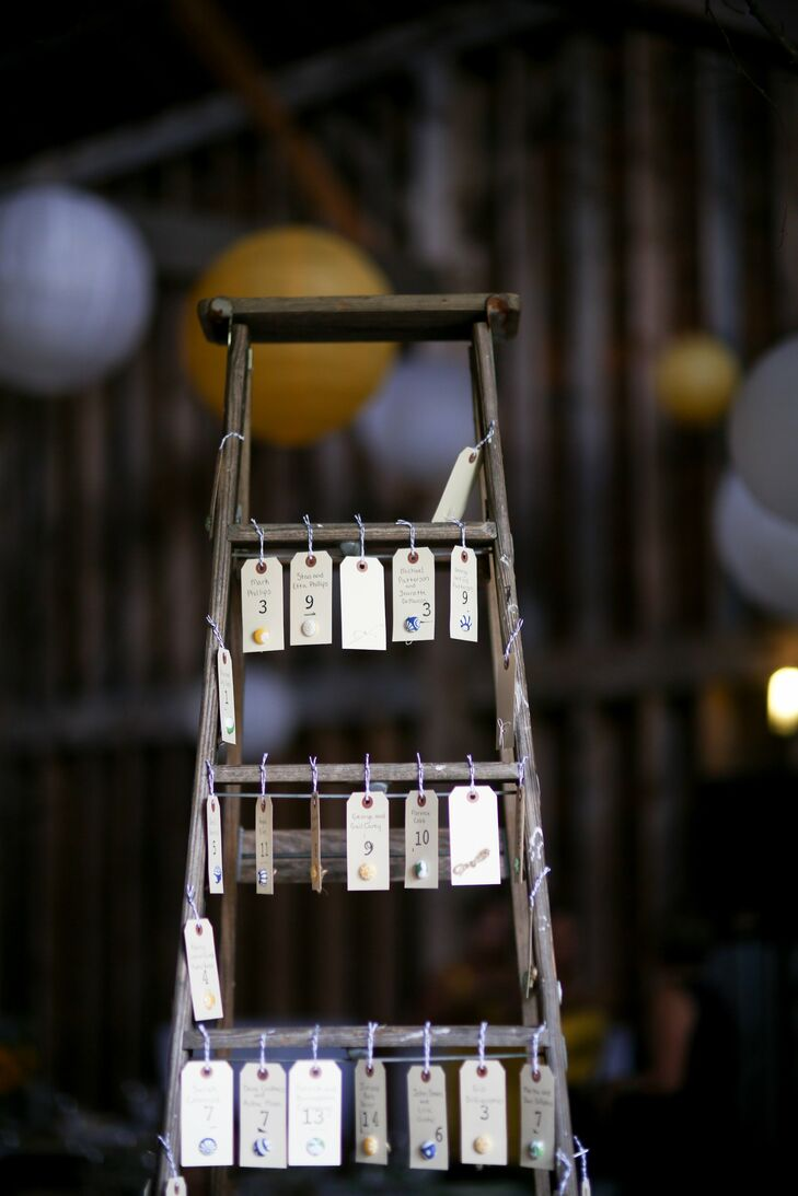 Caitlin and Jarred hand wrote each of the escort cards on gift tags and then hung them on a vintage wooden ladder.