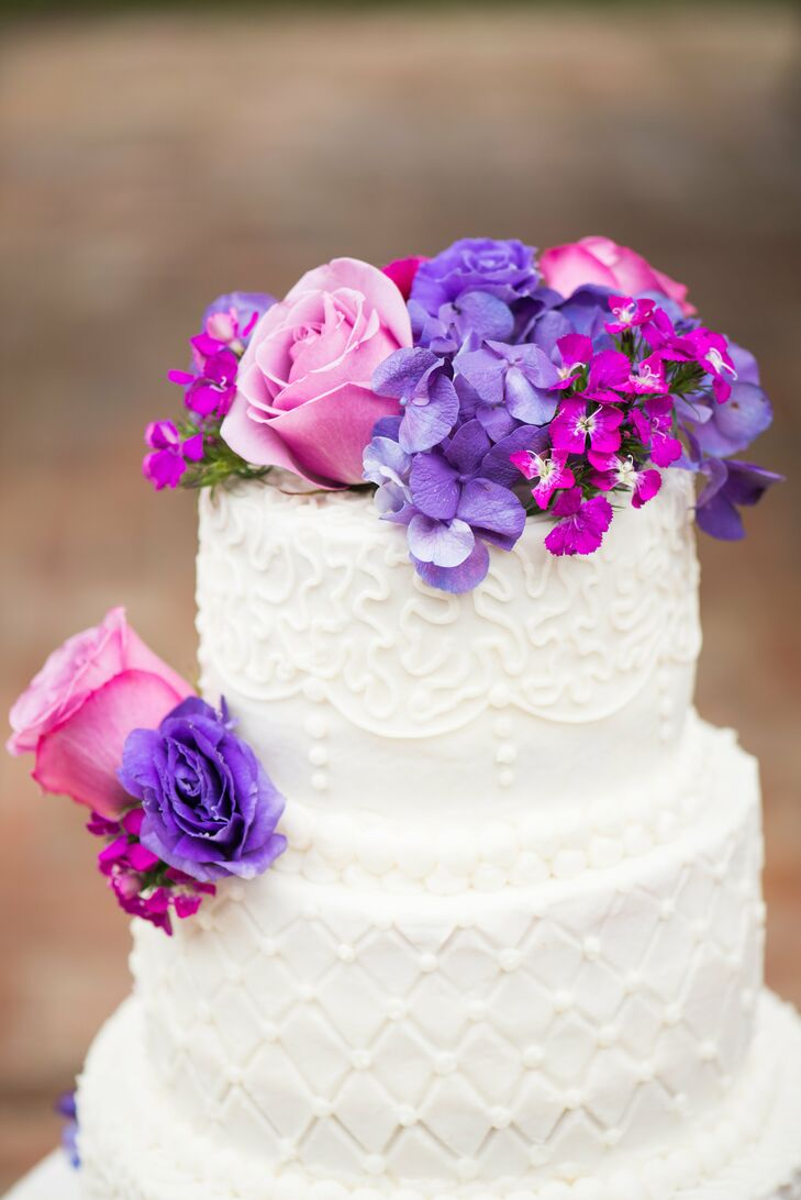 The traditional white round cake was topped with an array of purple and pink florals and piped in alternating cushion patterns and damask patterns.