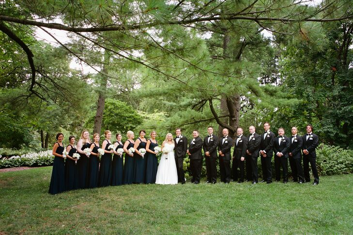 The bridesmaids wore long navy chiffon dresses. Sarah surprised them with statement necklaces in gold and crystal. The groomsmen wore classic black and white tuxes and the couple gifted them with monogrammed cufflinks.