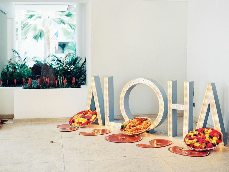 """White light-up marquee letters in """"Aloha"""" at wedding reception entrance"""