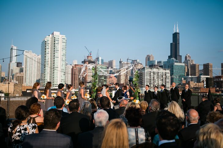 With Morgan Manufacturing offering a rooftop event space with breathtaking views of the Chicago skyline, the site for the ceremony was an obvious choice for Alyse and Vadim. The couple decorated the aisle with bundles of cheerful white and yellow blooms to create a cohesive feel from the ceremony to the reception and exchanged vows under a birch branch chuppah wrapped in lengths of white ribbon, greenery and sunflowers.