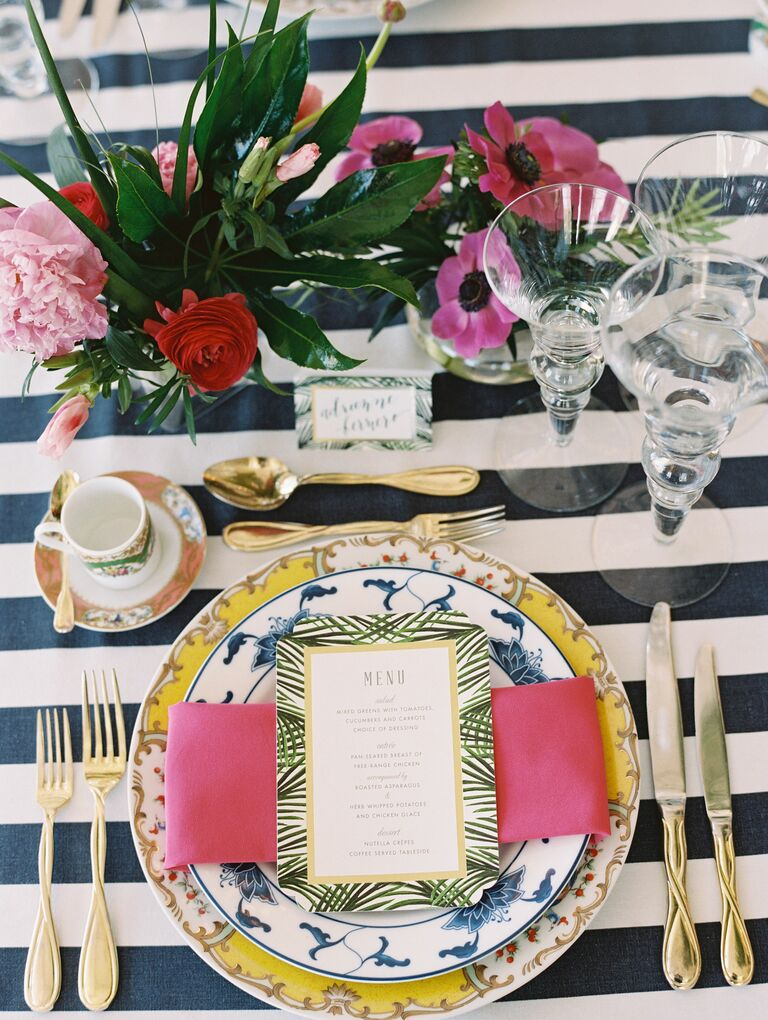 Place setting with gold flatware, striped linens and tropical centerpieces