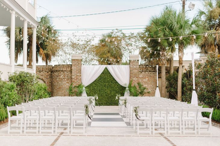 """The couple's courtyard ceremony was tastefully decorated with ivory curtains, string lights and floral arrangements embellishing the chairs that flanked the aisle. """"I wanted it to remain simple to really let the beauty of the Gadsden House shine,"""" Jennifer says."""
