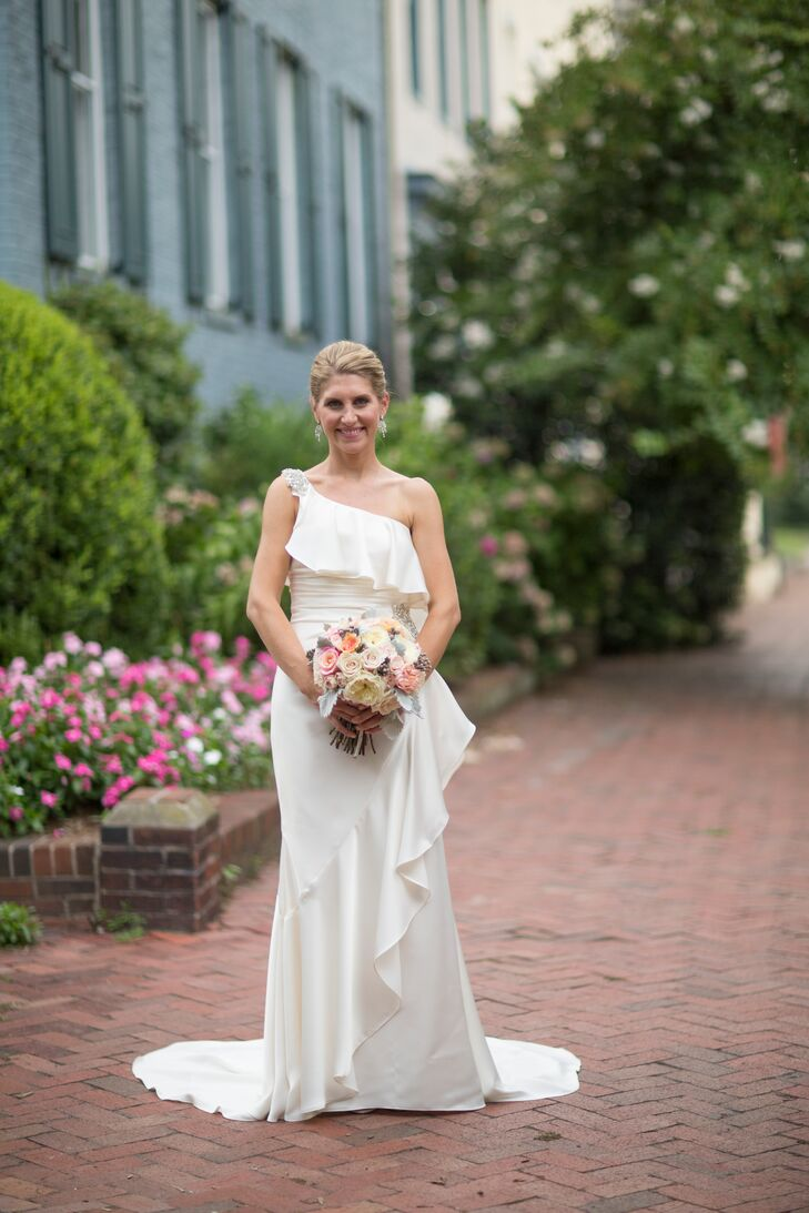 Beth wore a one shoulder Maya Couture wedding dress draped with angled ruffles. The shoulder was decorated with rhinestones and the dress was fitted around the waist.