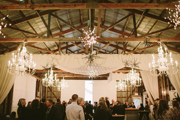 """After the couple said their """"I do's,"""" they invited guests to enjoy cocktail hour in the rustic barn. Panels of airy white fabric, ivory chandeliers and bursts of fairy lights brought an air of elegance and whimsy to the barn's country charm."""