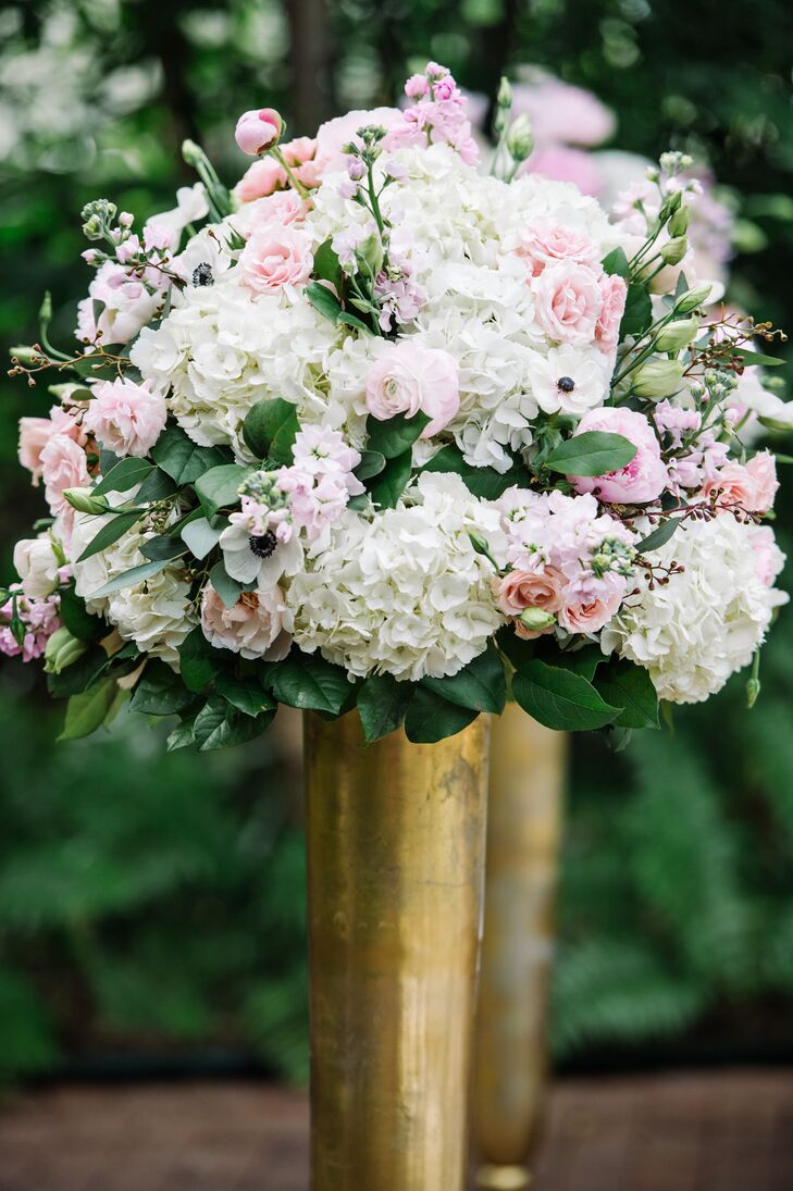 The ceremony aisle was framed with four gold vases filled with pink roses and peonies and white hydrangeas and anemones.