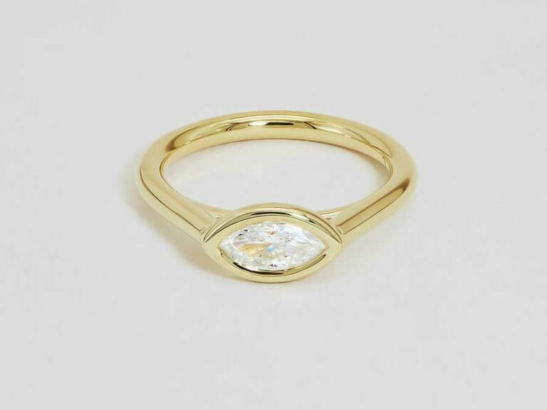 Marquise cut bezel set yellow gold engagement ring