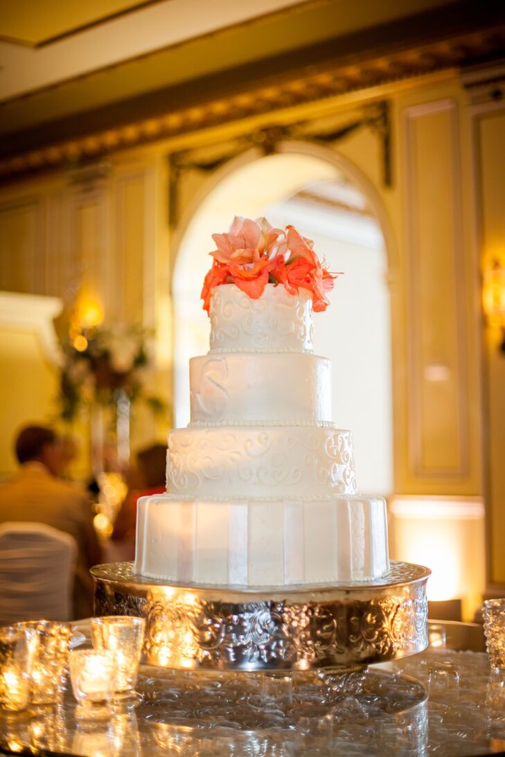 Melissa and Casey enjoyed a four-tier white vanilla bean wedding cake topped with coral flowers and made by The Broadmoor.
