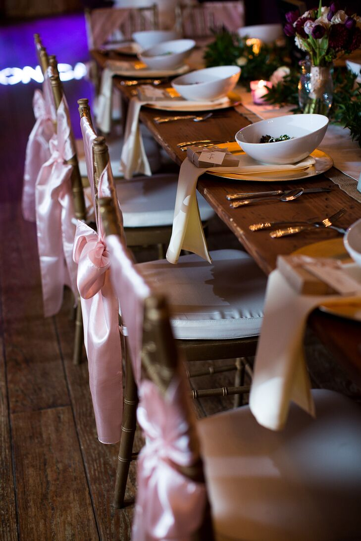 At the reception, chairs were decorated with silk pink ribbon and neatly set with napkins folded over the table.