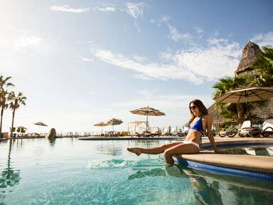a woman sitting on the edge of a pool splashing her feet and laughing in cabo san lucas mexico