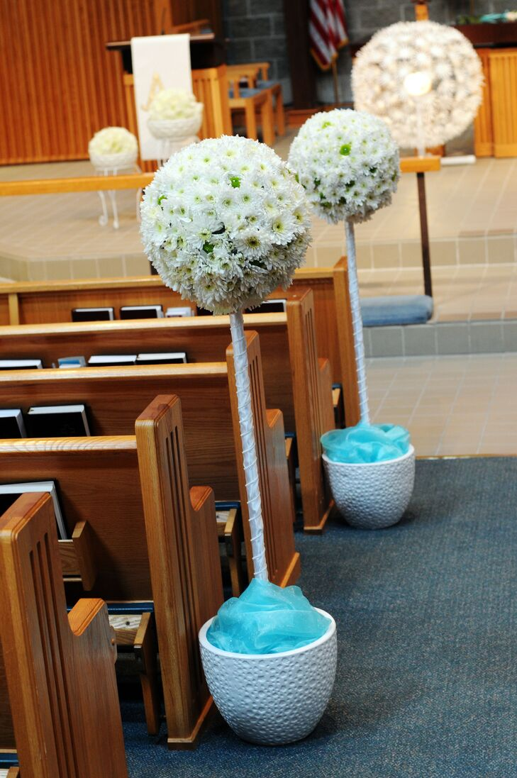Tall spider mum arrangements lined the aisle of Carmel Lutheran Church. Turquoise tulle at the base of every decoration added a pop of color.