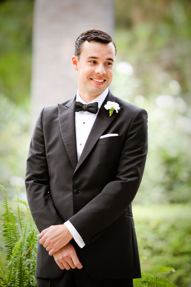 John watched his bride walk down the aisle during the wedding ceremony. He wore a vintage-inspired black tuxedo from the Great Gatsby Collection by Brooks Brothers, with a white button-up dress shirt and a black bow tie.