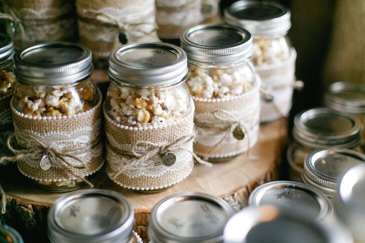 """Katharine and Marc's favors were DIY mason jars filled with homemade caramel popcorn. Katharine made the popcorn, while her mother helped decorate the mason jars in burlap and lace with a little """"love"""" charm."""
