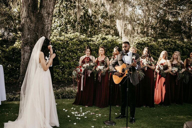 Groom playing guitar and singing song during ceremony