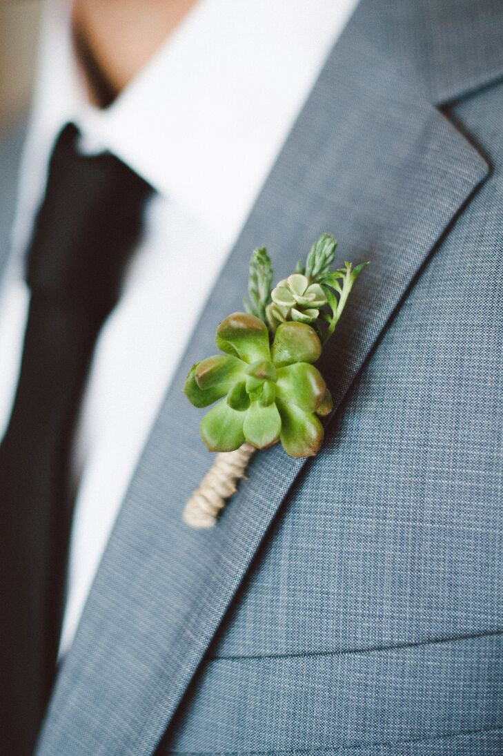 Chris wore a boutonniere made up of a large green succulent surrounded by smaller succulents that were tied together and pinned to his light gray lapel on his suit. He wore a white collared shirt under his jacket with a simple black tie.