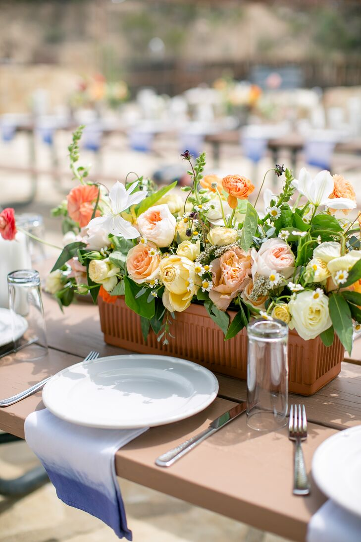 Designed with Valerie and Taylor's family-style picnic table reception in mind, the centerpieces were long and narrow in style. They included roses, ranunculus, Icelandic poppies, foxgloves, snapdragons, tulips, clematis, chocolate cosmos, chamomile, eucalyptus, bay leaves and olive leaves. Potted cacti and pillar candles filled in the spaces between the wild floral centerpieces.