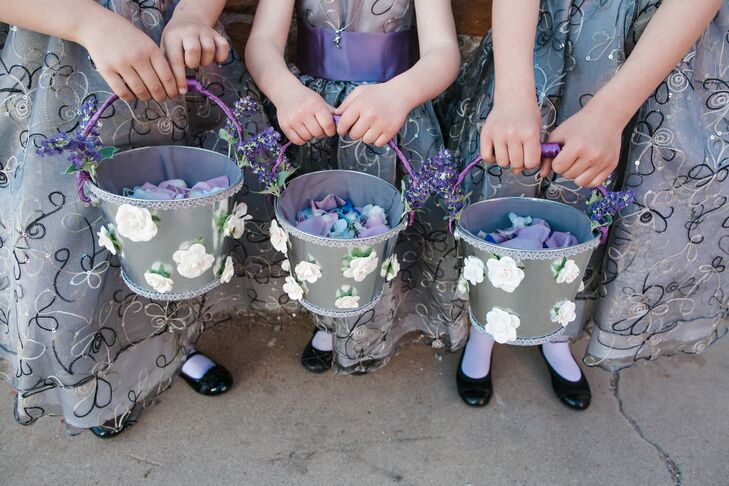 Gloria made the baskets for the flower girls' petals. She decorated silver pails with white and purple flowers to match the flower girls' gray dresses with sequined flowers.