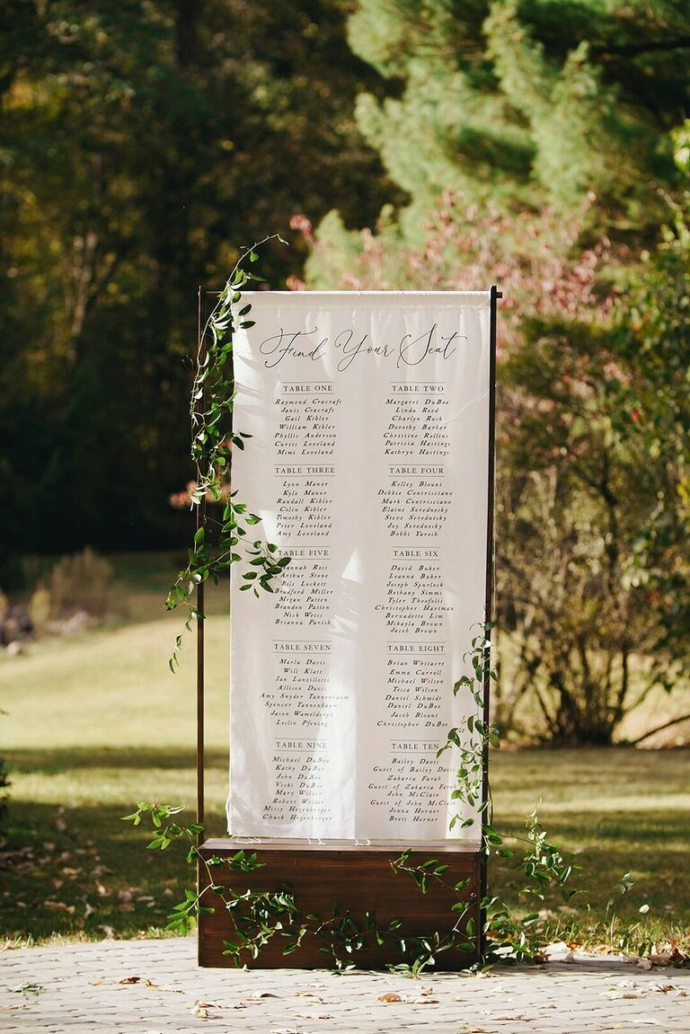 Linen seating chart with calligraphy and greenery decorations