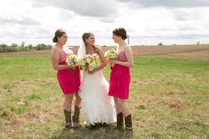 The bridesmaids wore pink strapless dresses with cream Chantilly lace detail. Each also sported cowboy boots with gemstone boot bands. The bridesmaids held matching spring flower bouquets made of yellow and white daisies and pink calla lilies.