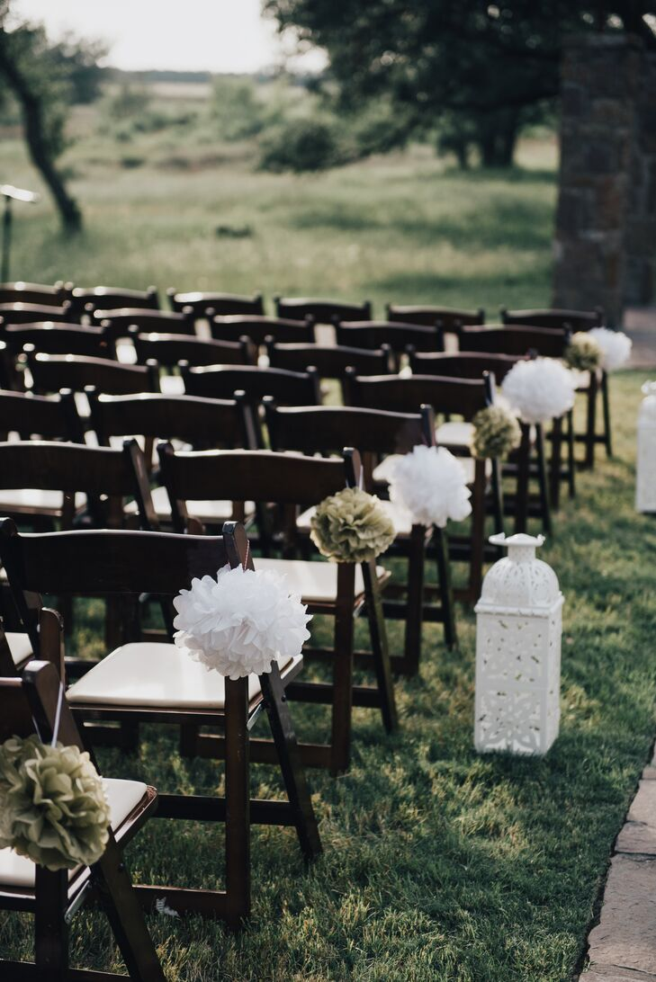 The ceremony took place outdoors on the lawn of Ma Maison in Dripping Springs, Texas. The aisle seats were decorated with alternating white and green tissue-paper pompoms and white lanterns.