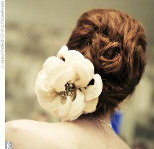 To prepare for an evening of dancing, Dixie's stylist pulled her hair into a loose updo after the ceremony. The brooch in the center of the flower comb was Dixie's great-grandmother's.