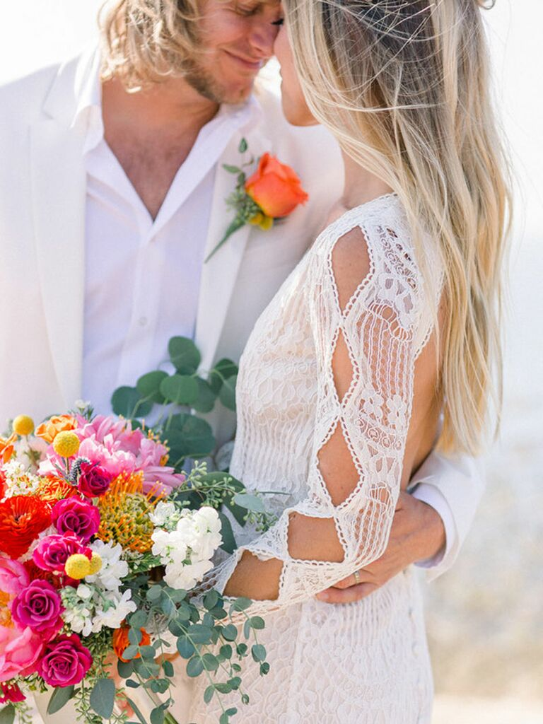 Bride and groom wearing white wedding outfits with pink and orange summer wedding flowers