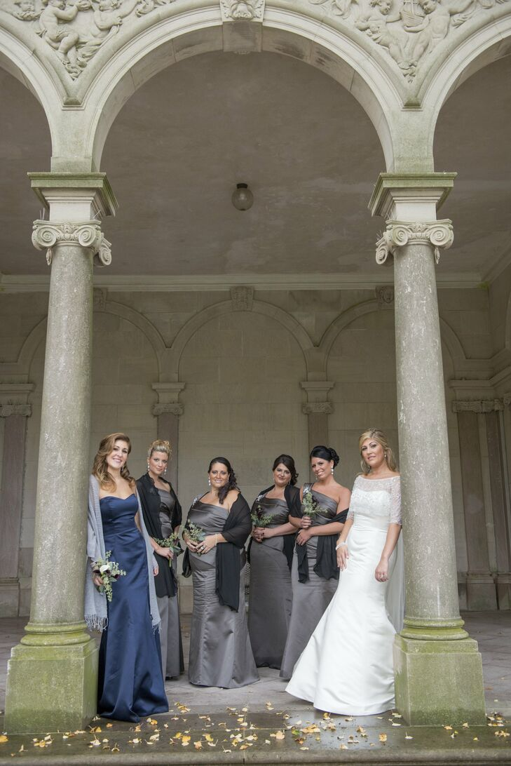 The bridesmaids wore one-shoulder satin Vera Wang dresses in charcoal gray, and the maid of honor wore a strapless navy gown.