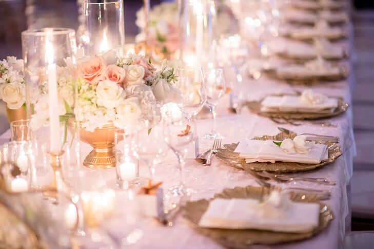 """Mirror-topped tables offered a """"glam glow,"""" thanks to centerpieces of hydrangeas and roses, candles and gold burst chargers with ivory linen napkins."""