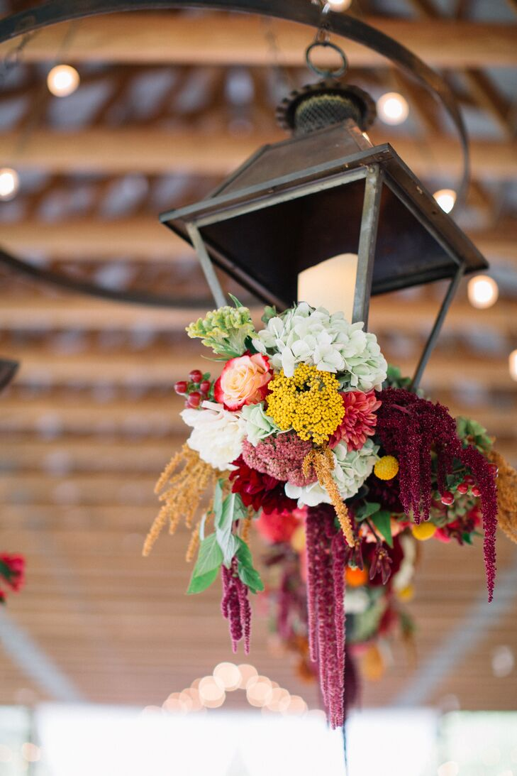"""One of my favorite designs of the night was our floral chandelier, which hung above the center of the dance floor,"" Katie says. Three large, vintage lanterns filled with tall candles were suspended from the ceiling and fresh fall flowers whimsically cascaded out of the bottom."