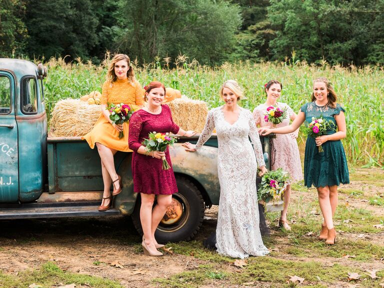 Bride and bridesmaids with pickup truck and hay fall wedding