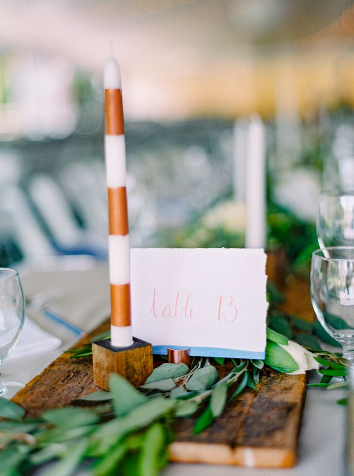 While the couple opted against farm tables, they used lengths of foraged wood to achieve a similar effect. The wooden panels gave way to flickering table candles wrapped in copper-striped taper candles and bundles of fresh greenery for a beautifully bohemian look.