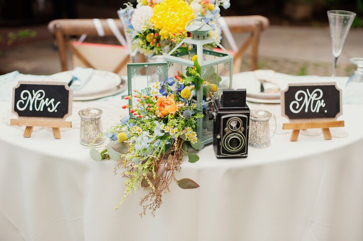 "At the sweetheart table, two chalkboard signs reading ""Mr."" and ""Mrs."" labeled the seats where Katy and Adam sat. The centerpiece had an overflowing flower arrangement spilling out of the green lantern, positioned next to a vintage black camera."