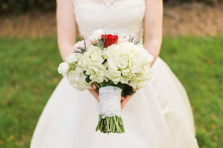The Flower Shop designed a classic bouquet for Patricia with both natural and sentimental charm. White hydrangeas surrounded pink and white roses and greenery, and all were placed in a white lace wrap. To honor her mother, who passed away two years ago, Patricia had a  single red rose near the center the arrangement.