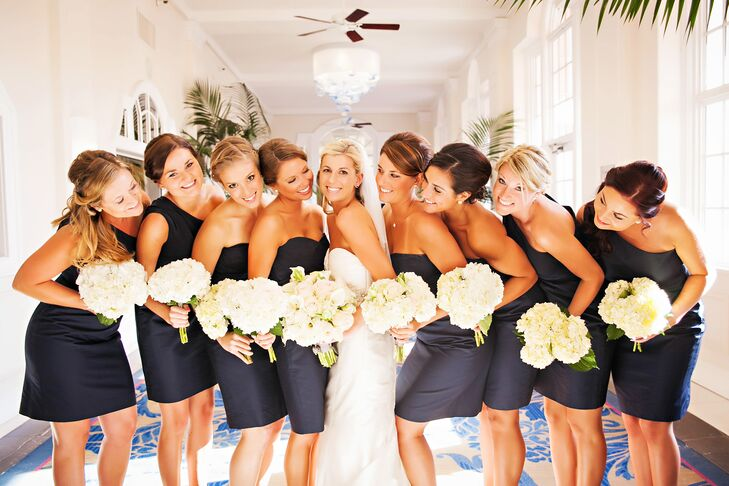 Kelly's bridesmaids wore navy cotton J.Crew dresses that were inexpensive and could be worn again. As a gift, the couple paid for the girls to get their hair done and gave each bridesmaid gold Kate Spade pearl earrings with a rope design.