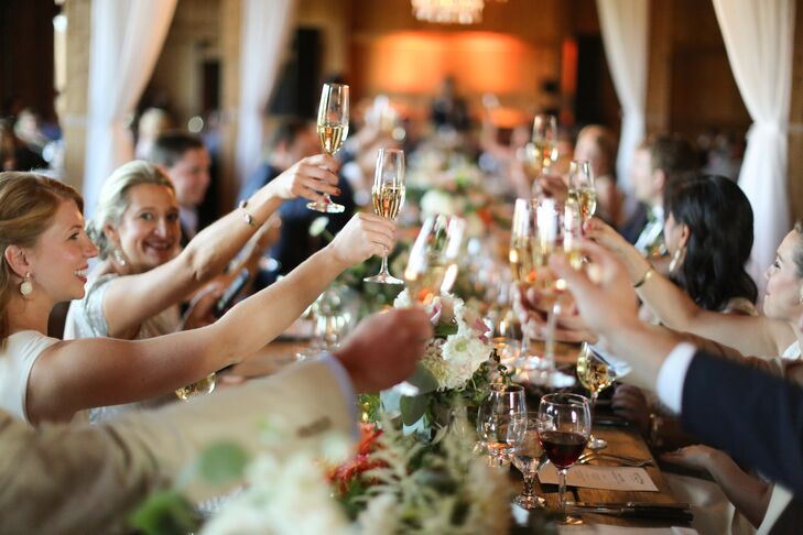Guests raised their champagne glasses to toast the newlyweds at the reception.