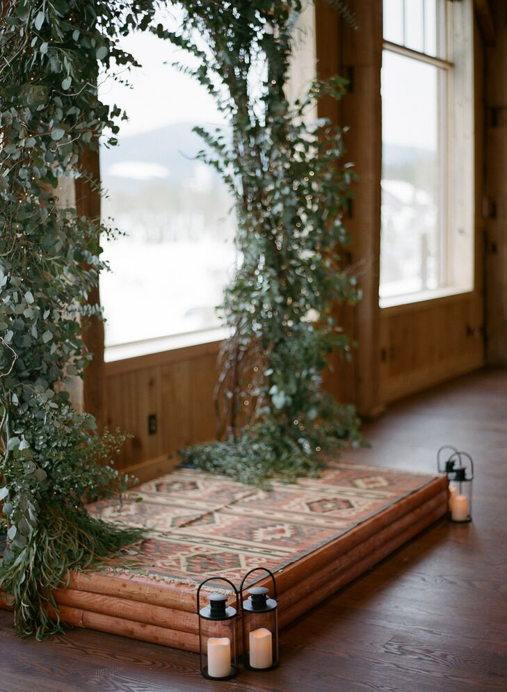 "Jeff built a log cabin-style stage at the couple's house in Denver, Colorado, and transported it to the wedding venue. ""We had a lighted, floral arch built over the stage that was placed in front of the large windows on the west side of the barn, perfectly framing the falling snow during the ceremony,"" Charlotte says."