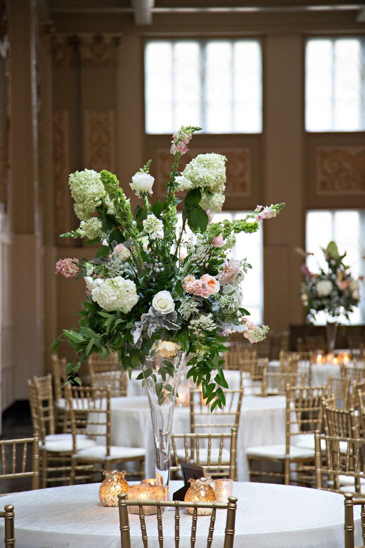 The couple had their florist design to types of centerpieces for the reception tables. The tall centerpieces were arranged in trumpet-shaped glass vases and featured textured bunches of hydrangeas, roses and bells of Ireland.