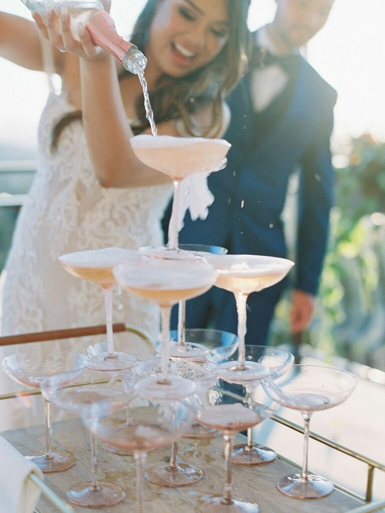 Bride pouring champagne over glasses arranged in a tower
