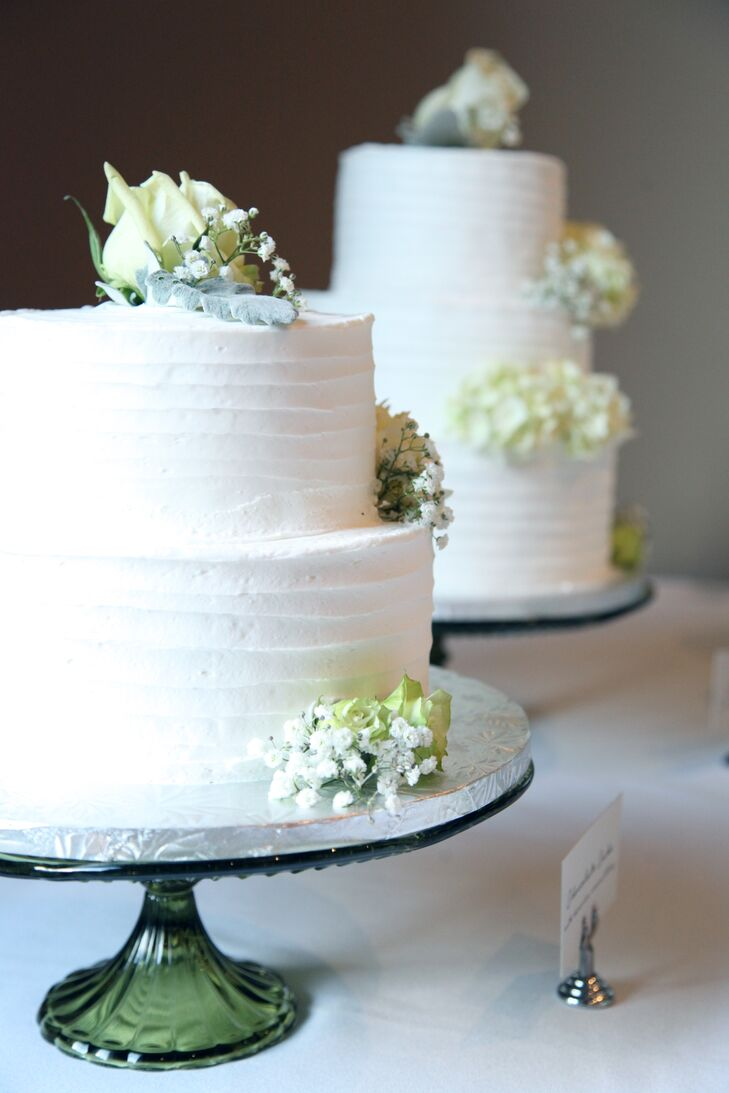 Instead of one traditional wedding cake, Brooke and Brad enjoyed three white buttercream-decorated wedding cakes. We love the texture on each tier! Each cake was topped with green roses and baby's breath for a little added romance. One cake was a spice cake with cream-cheese icing, another was vanilla cake with strawberry filling and the last was chocolate cake with Bavarian cream icing.