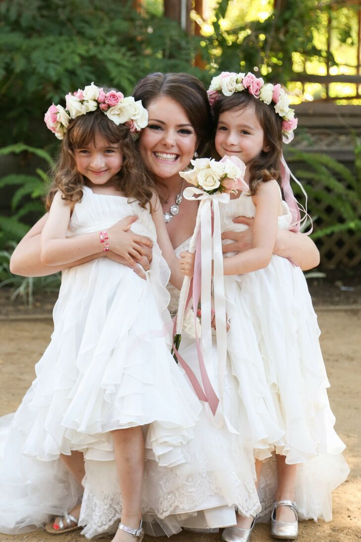 Samantha held her two flower girls close to her, who wore ivory dresses and flower crowns made of pink and ivory roses.