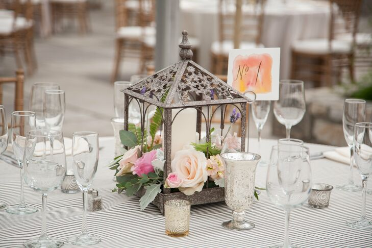 An arrangement of pastel roses were displayed in a iron mini gazebo.