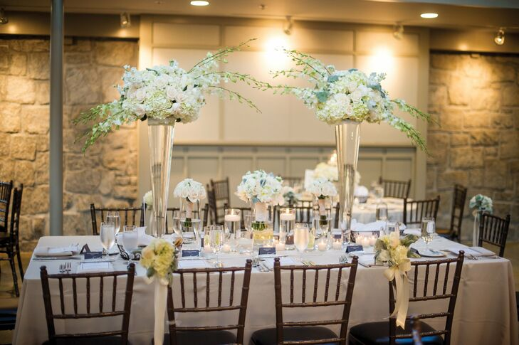 Tall glass vases were filled with white and ivory spray roses, peonies, hydrangeas, stock and dusty miller.